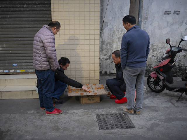 men playing a game of xiangqi on Mazhou Street (麻洲街) in Zhongshan, China