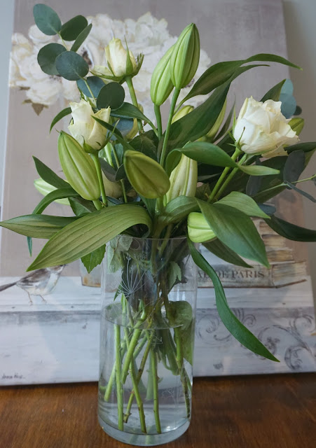 photo of a bouquet of closed oriental lilies and avalanche roses