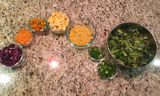 Photo of bowls of chopped veggies in containers on a counter arranged like a rainbow, including red cabbage, orange bell pepper, yellow cherry tomatoes, yellow summer squash, corn kernals, green onions, and mixed salad greens. https://trimazing.com/