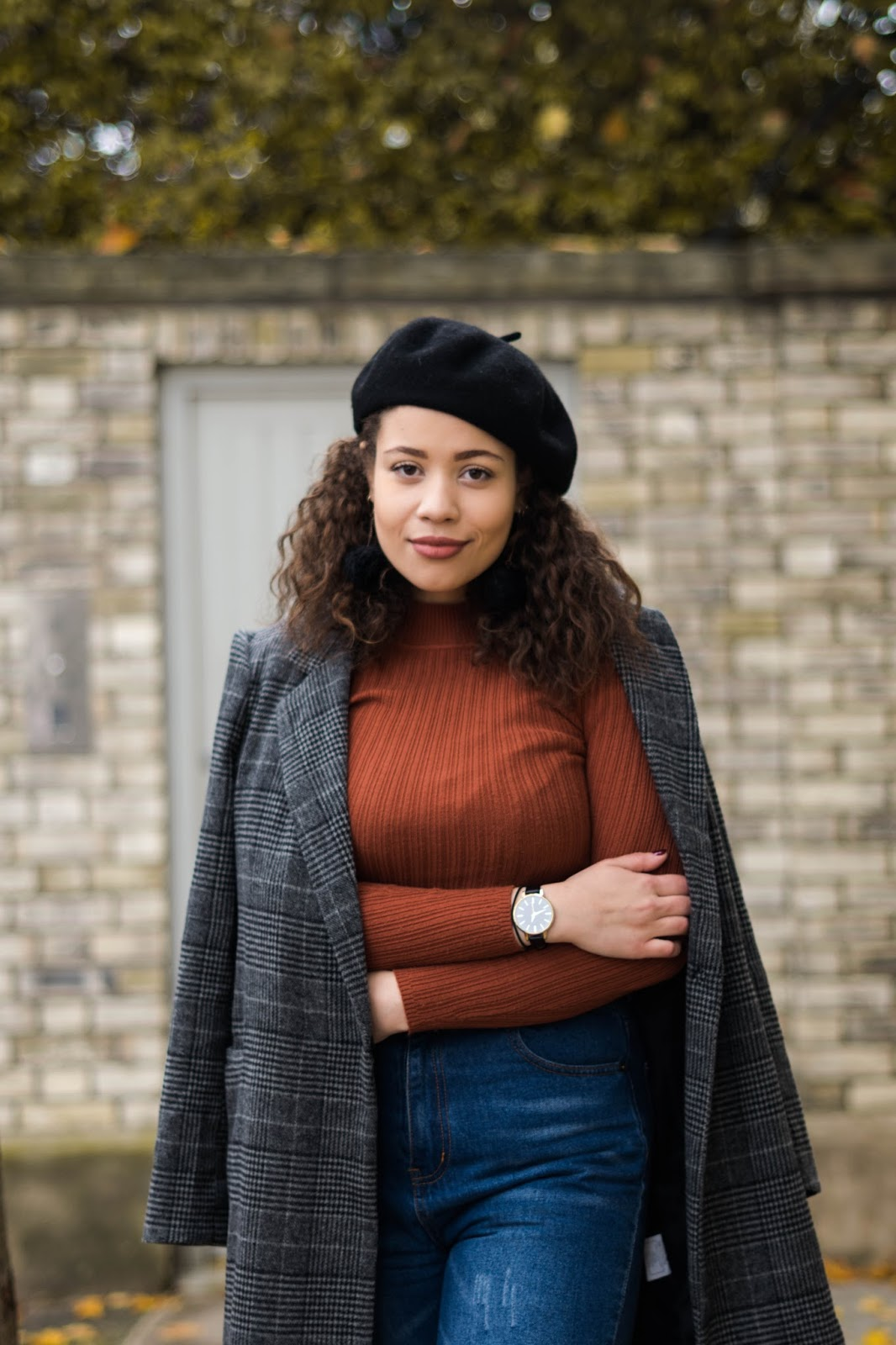Eboni wearing a black beret with an autumnal jumper and coat