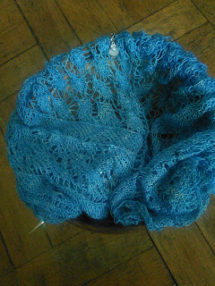 a blue lace shawl live on a circular needle, tucked into a wooden yarn bowl.  There is a stitch marker with a shell charm clipped into the work.