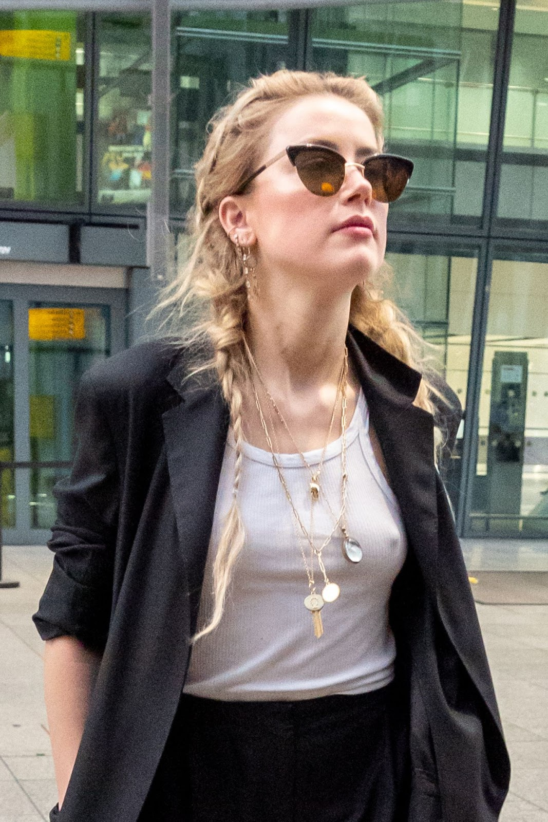 Amber Heard goes braless at Heathrow Airport