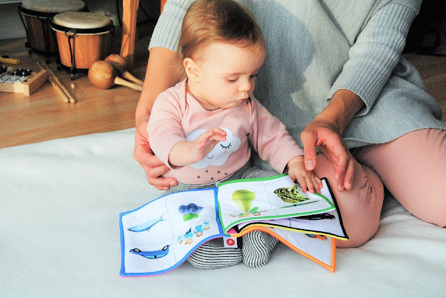 A woman reading a book with a baby