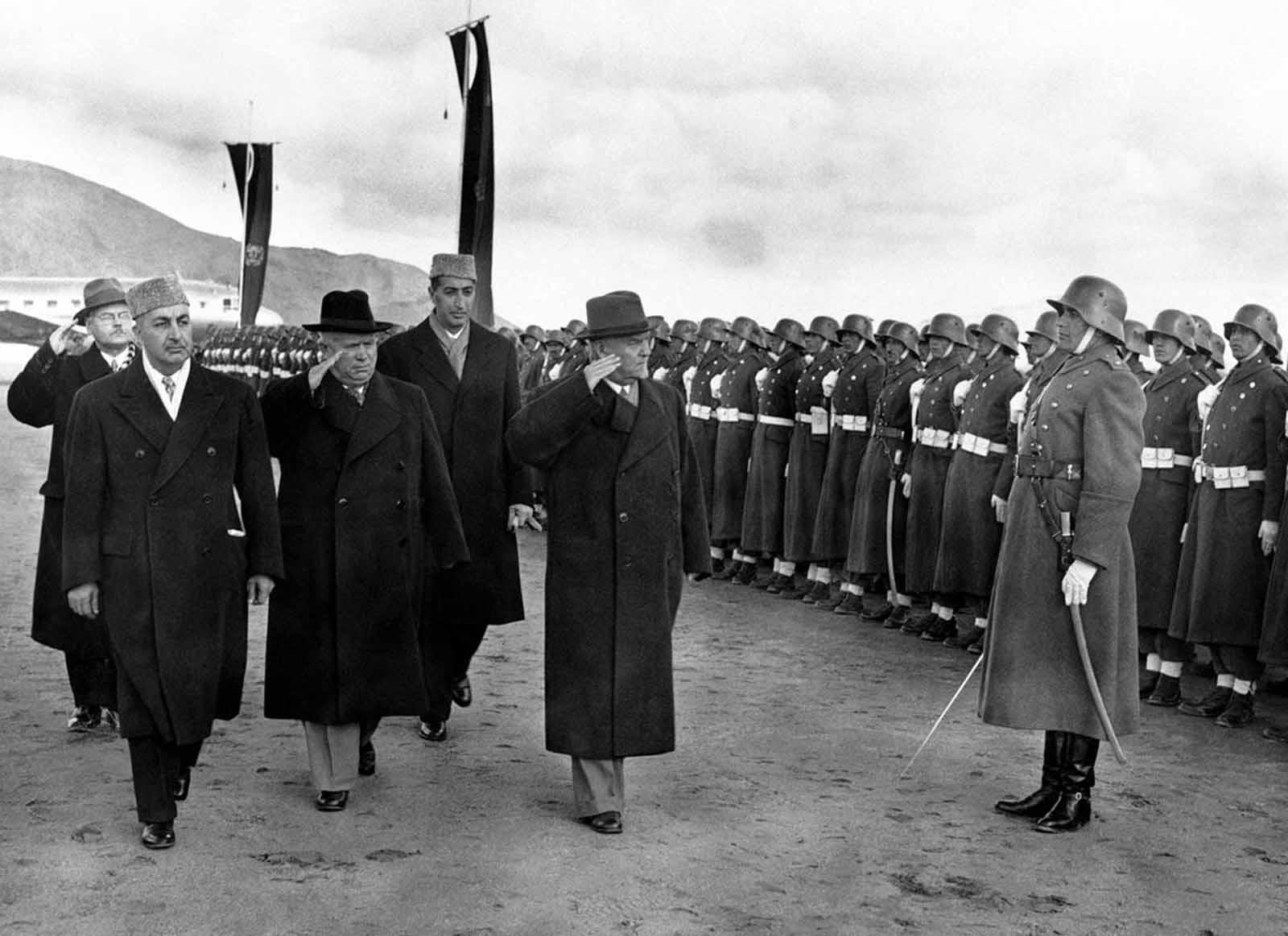 El líder soviético Nikita Khrushchev (sombrero negro) y el mariscal Nikolai Bulganin revisan a una guardia de honor afgana vistiendo viejos uniformes alemanes, a su llegada a Kabul, Afganistán, el 15 de diciembre de 1955. A la izquierda está el primer ministro afgano, Sardar Mohammed Daud Khan, y Detrás, en cap, el ministro de relaciones exteriores, el príncipe Naim.