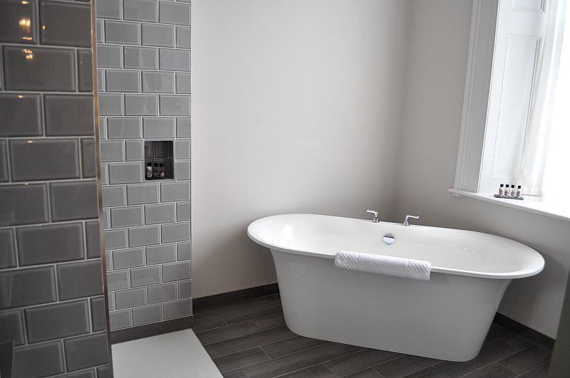 grey subway tiles and modern bath tub