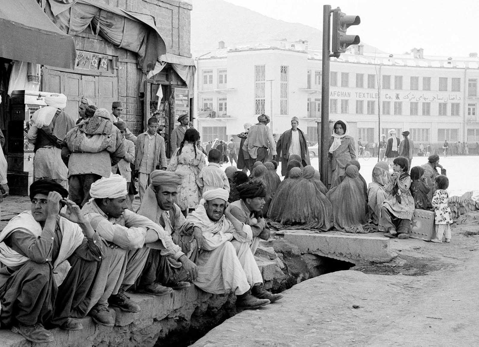 A modern traffic light stands incongruously amid burqa-clad women sitting on a Kabul street corner with their backs to their men on May 25, 1964.
