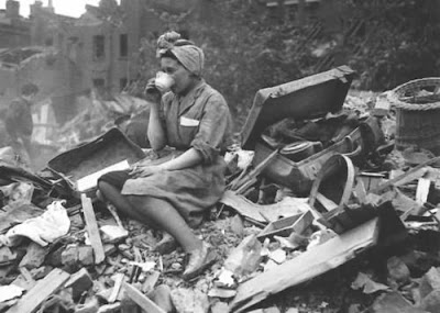 woman sadly drinking tea in the wreckage of her home in London during the Blitz