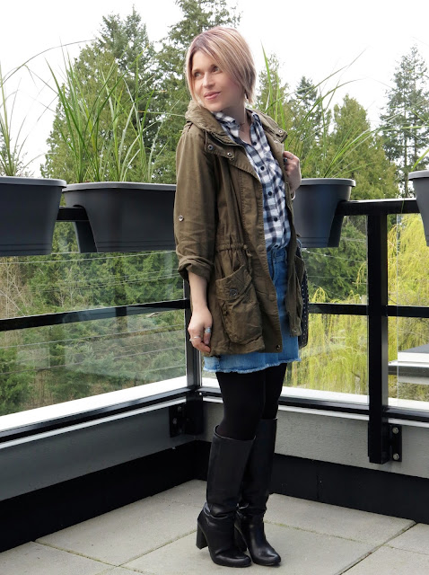 styling a denim miniskirt with a plaid shirt, tights, tall boots, and an army-style parka