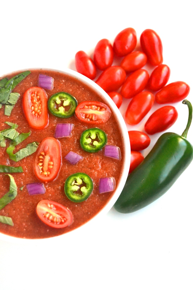 Spicy Gazpacho Soup takes 10 minutes to make and is full of flavor with fresh jalapenos, tomatoes, cucumber, onion, bell peppers and basil for a light and fresh meal! www.nutritionistreviews.com