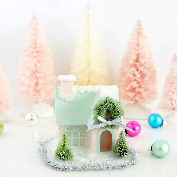 glittered paper putz house displayed with pink and ivory bottle brush trees and ornaments