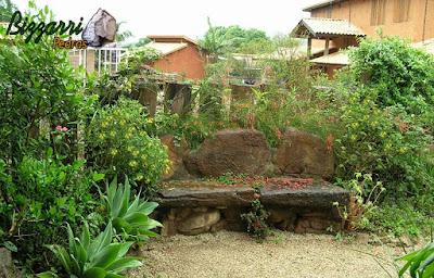 Banco de pedra no jardim, com pedra moledo, com a execução do paisagismo com o piso com pedregulho do rio.