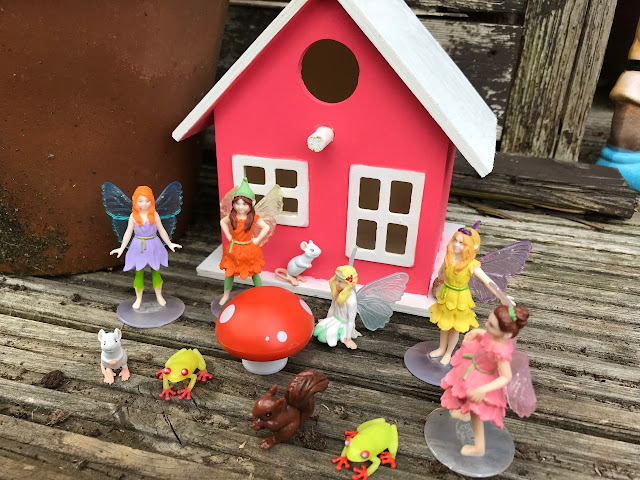 Painted bird house as a fairy house, with fairies and mini animals in front of it