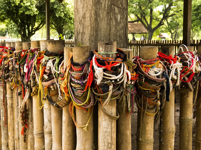 Friendship bracelets around a mass grave at the Killing Fields of Choeung Ek in Phnom Penh Cambodia