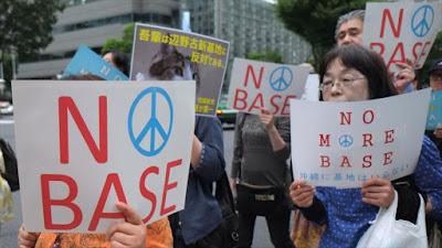 """Manifestantes japoneses llevan cárteles donde se lee """"No más bases de EE.UU."""", 12 de junio de 2016."""