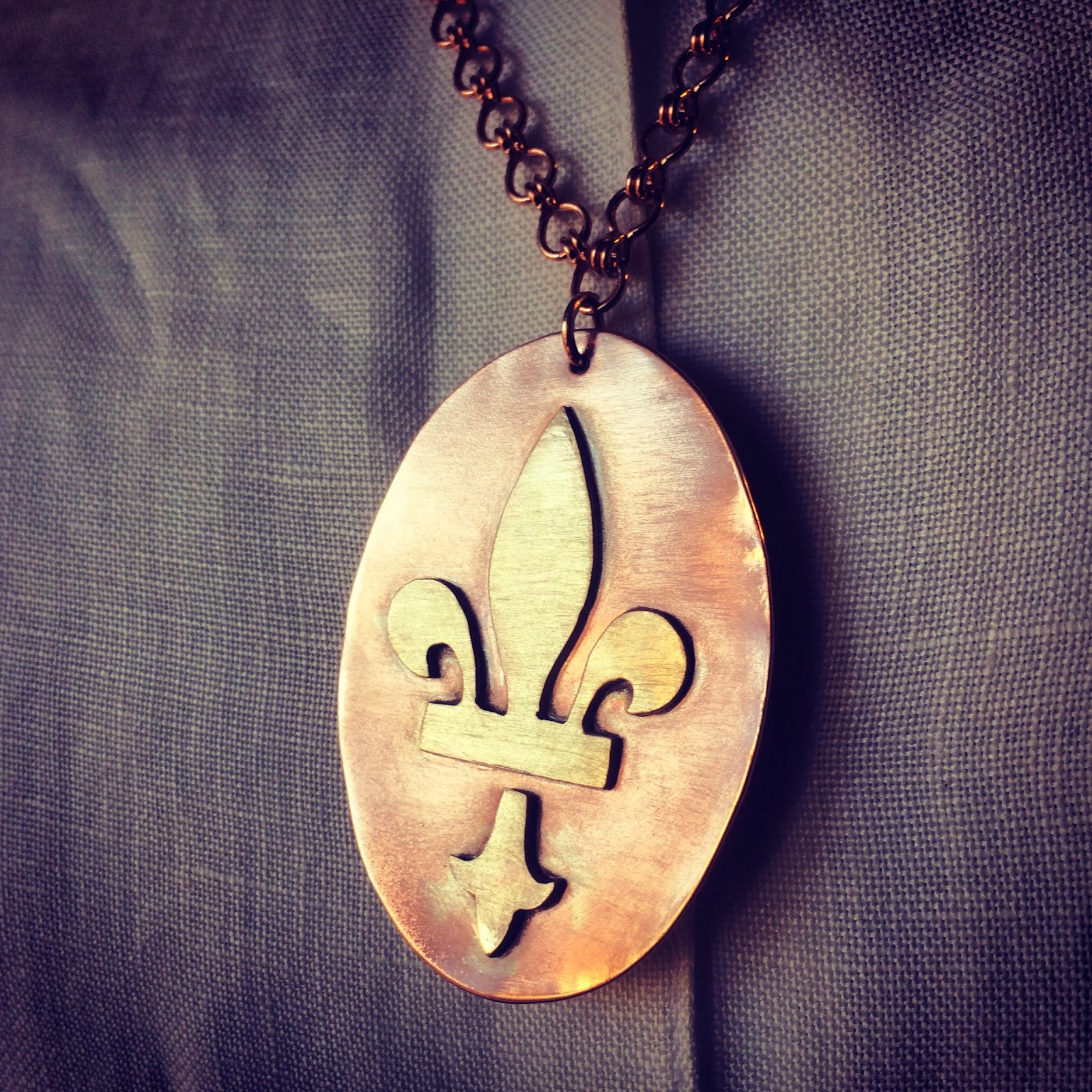 Sweat soldered brass fleur de lis to copper oval backing