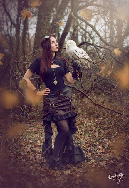 Steampunk woman wearing black and brown steampunk clothing (skirt, bolero jacket, goggles, pocket watch) holding a white owl in the woods/forest