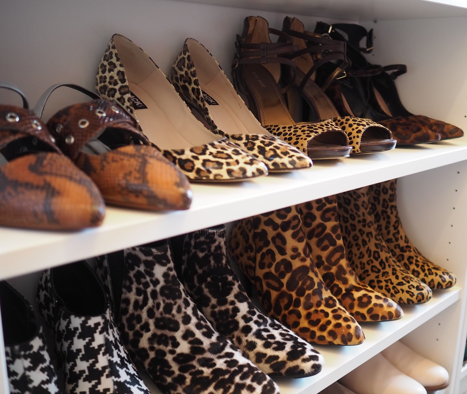 Walk in closet with white Ikea Billy bookcase as shoe storage, animal print shoes