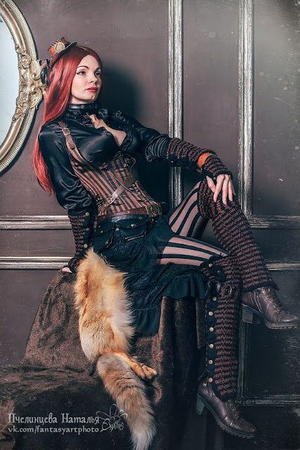 Redheaded woman wearing steampunk clothing. corset, skirt, stripes, etc.