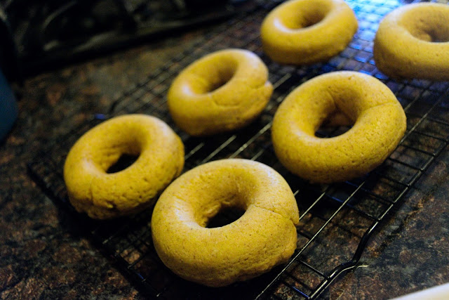 The baked donuts on a cooling rack, on the counter.