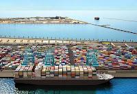 Konteynerler ile dolu bir deniz limanına yaklaşmış bir yük gemisi