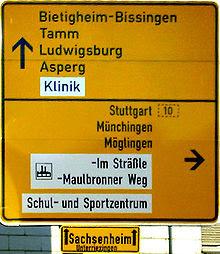 Exemplo da fonte DIN. A imagem é a placa de transito da Alemanha (fundo amarela com fonte preto). A Fonte ela não é muito larga e tem um bom espaçamento entre as letras.