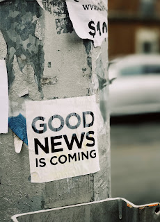 A pole with a sign on it saying 'good news is coming'