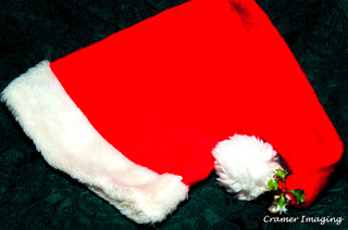 Cramer Imaging's professional quality fine art photograph of a red and white Santa hat on a green background
