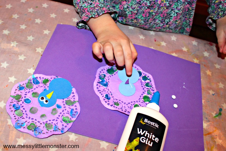 Paper doily peacock craft for kids with fingerprints. Easy enough for toddlers and preschoolers, this activity makes a great addition to a bird themed project.