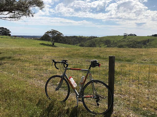 Bicycle sitting next to a fence, overlooking green rolling hills