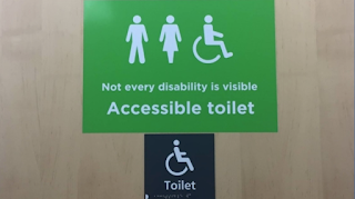 Asda supermarket sign with three symbols of a man, woman and wheelchair user with the words Not every disability is visible and Accessible Toilet