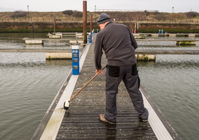Photo of Phil scrubbing a pontoon