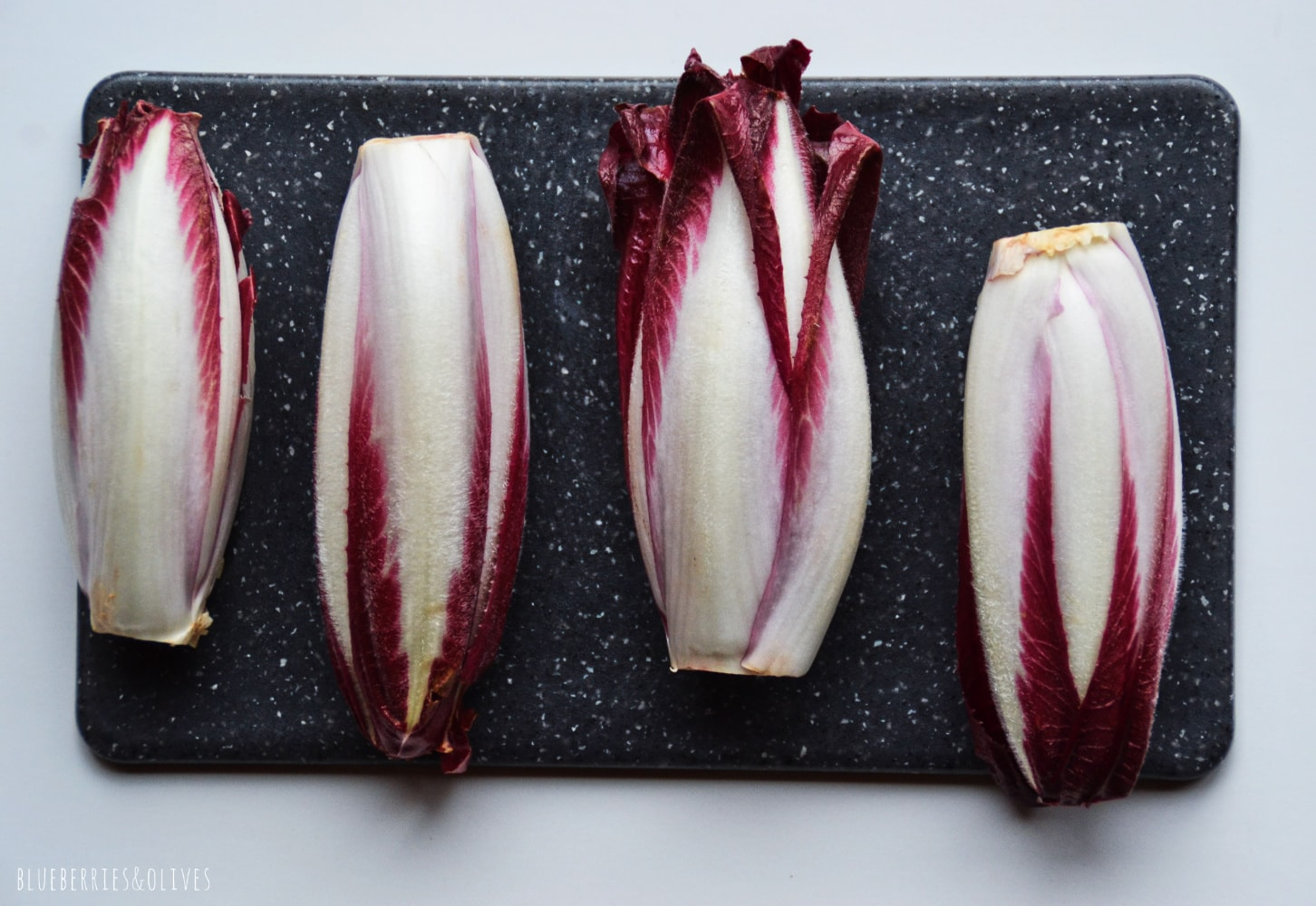 FRESH CHICORY OVER A BLACK GRANITE CUTTING BOARD