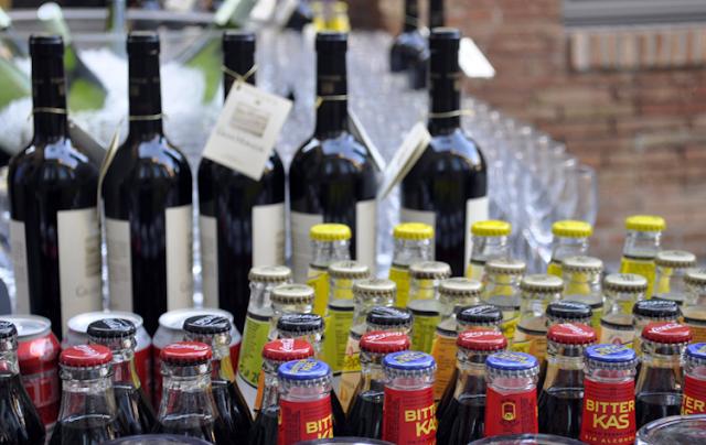 diversas botellas de refrescos y vinos junto a numerosas copas
