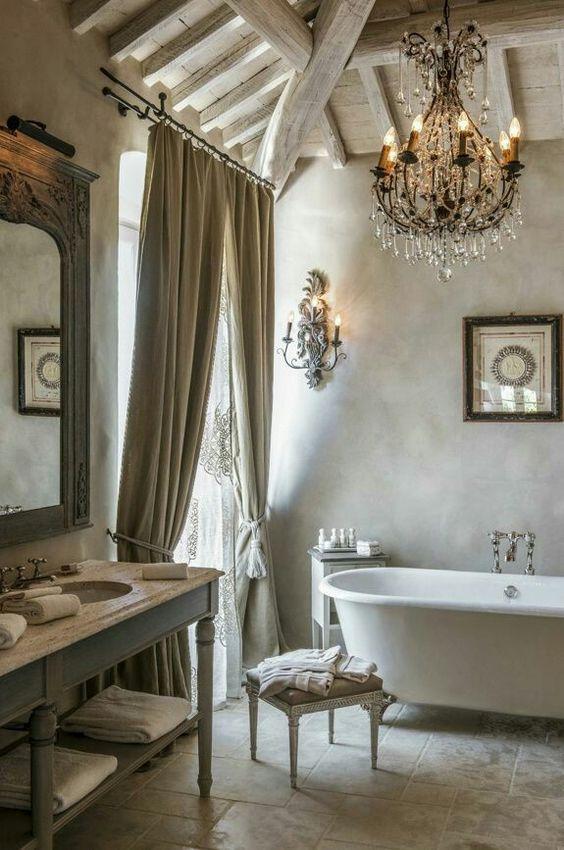 Elegant #Frenchfarmhouse bathroom with clawfoot tub, crystal chandelier, and stone floor