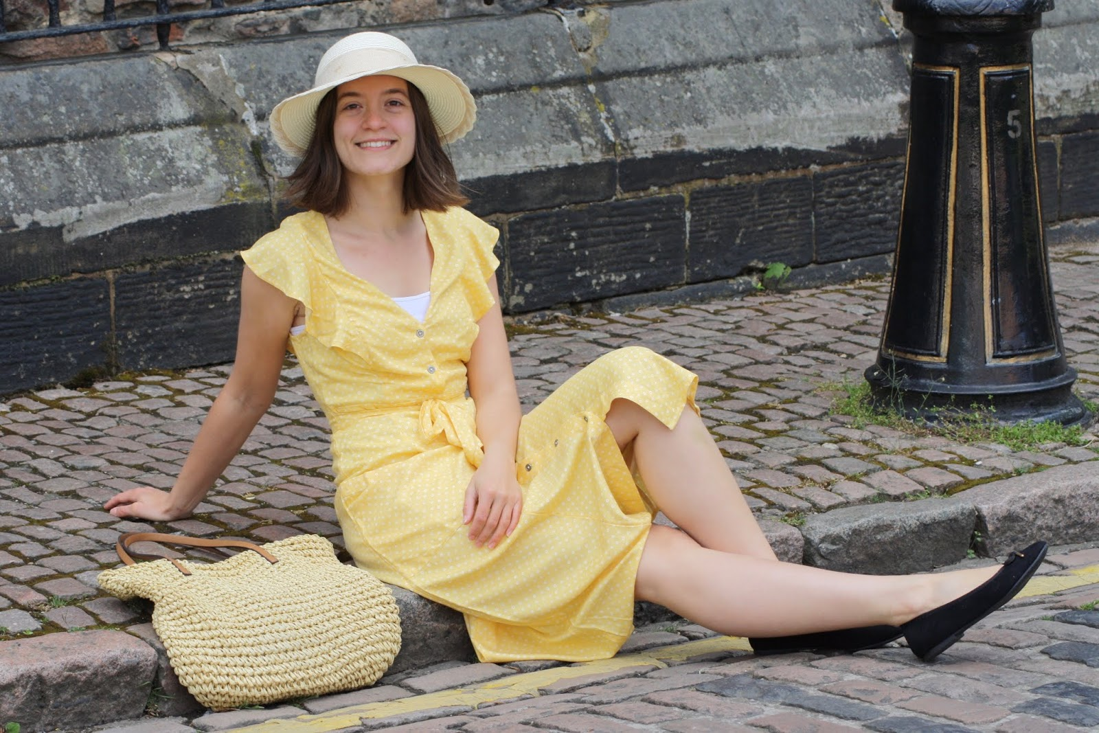 Abbey, seated on the pavement, wears a yellow floaty dress with cap sleeves, a straw handbag next to her