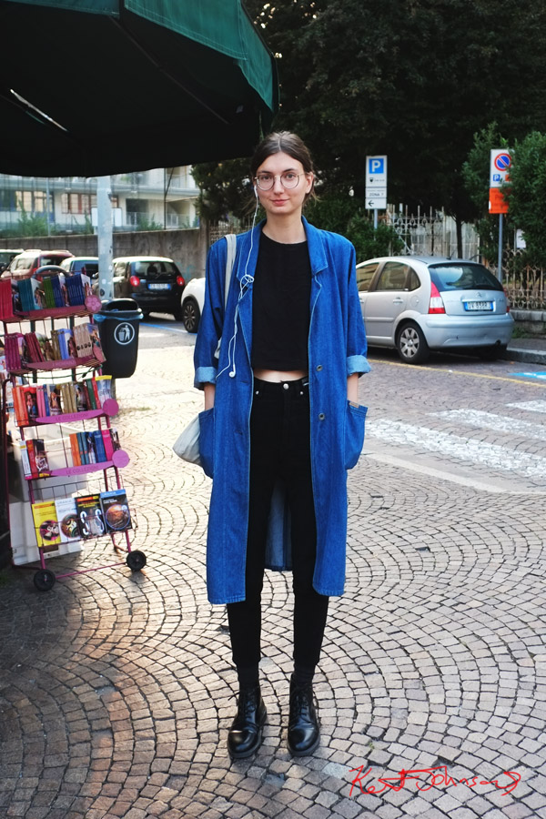 Como Street Style - black on black with long blue denim coat, round glasses. Photographed by Kent Johnson. Como, Italy,