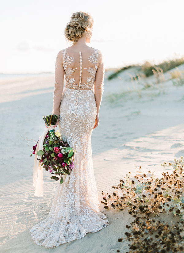 This beautiful sheer open back lace wedding dress is one of many wedding dresses from She Wore Flowers, the only bridal marketplace that is devoted to showcasing indie designers. This gown has beautiful lace detail and has a soft mermaid silhouette and long sheer sleeves.