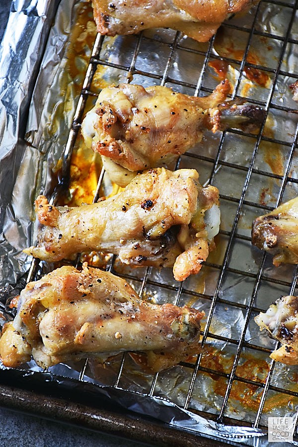 Fully cooked chicken wings on a rack in a baking sheet