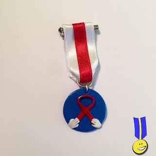 Medalla con fondo azul y lazo rojo cogido en cada extremo por unas manos en blanco