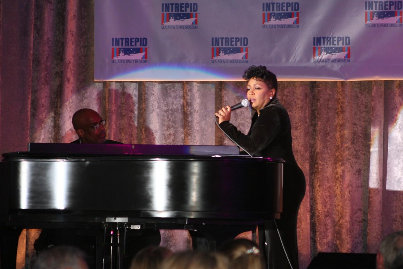 ピアノに凭れてマイクを持つアニタ・ベイカー