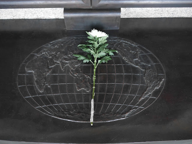 flower on top of an engraving of the Earth