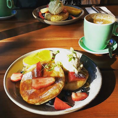 Plate of hotcakes and fruit, next to a mug of coffee at a cafe.