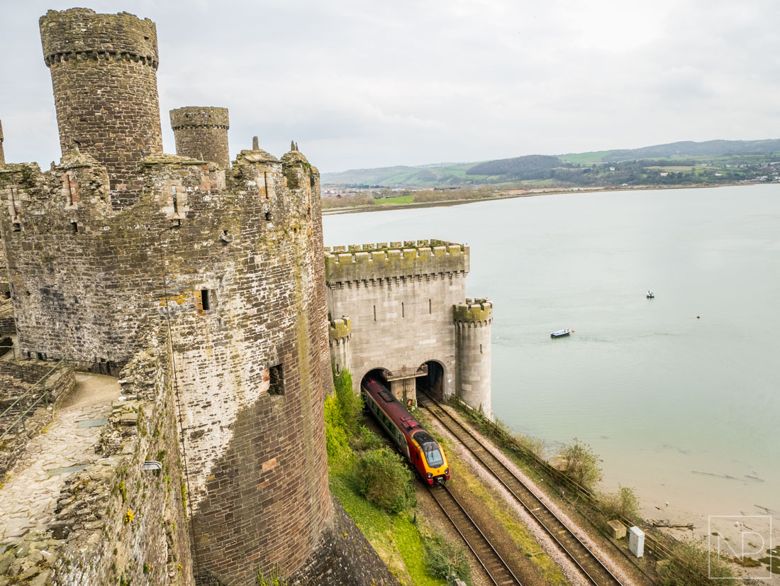 Train passing alongside Conwy Castle and suspension bridge
