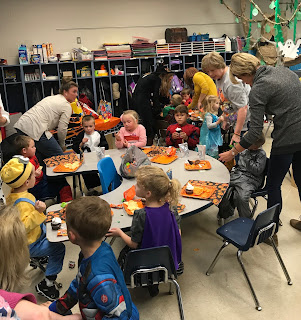 Group of students sitting at desks eating treats from Fall Festival