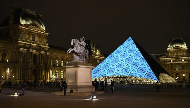 Images are projected onto the Louvre Pyramid in Paris at night to mark the opening of the Louvre Abu Dhabi Museum on Saadiyat Island, Abu Dhabi, November 8, 2017. AFP/Eric Feferberg