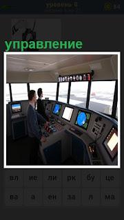 пульт управления судном, где стоят двое мужчин за мониторами