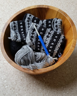 A wooden bowl with contents: grey and black balls of yarn, grey and black striped and dotty fingerless mitts in progress with a blue-handled crochet hook.