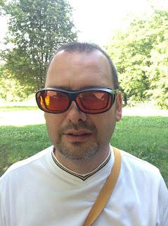 Fotografia do Luís a testar os óculos de lentes laranja por cima dos seus óculos habituais