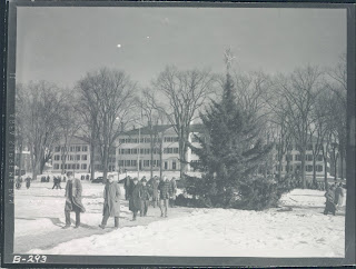 Black and white photo of college students walking to class on the green in the snow with the christmas tree in the background