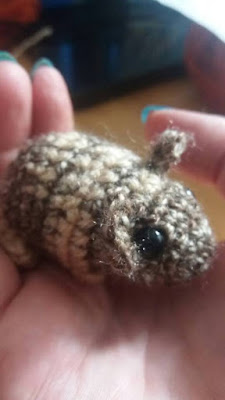 Hands holding a little crocheted grey mouse